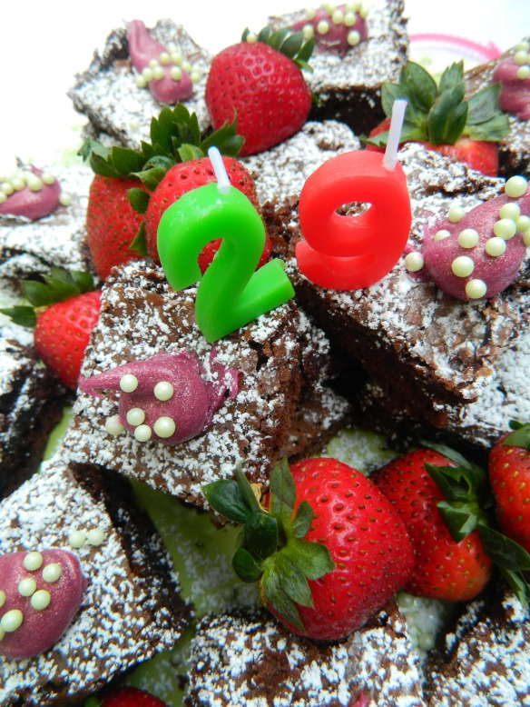 Bake brownies, sprinkle with powdered sugar, dot with colored frosting and sugar pearls. Accent with strawberries and add the numbers.