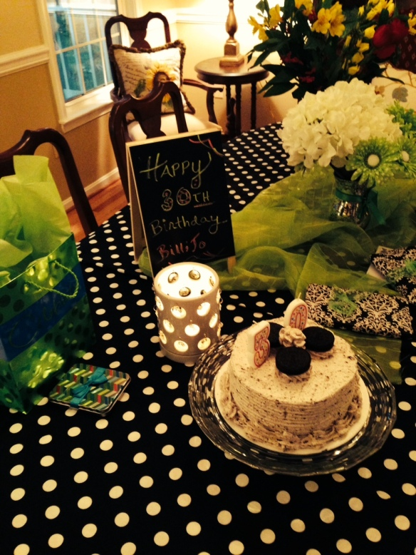 This all started with a black and white store-bought cake.  The chalkboard easel appears again with candles, presents wrapped in black and white paper white flowers (silk), polka dot fabric remnant, and green accents with fabric and tissue paper.